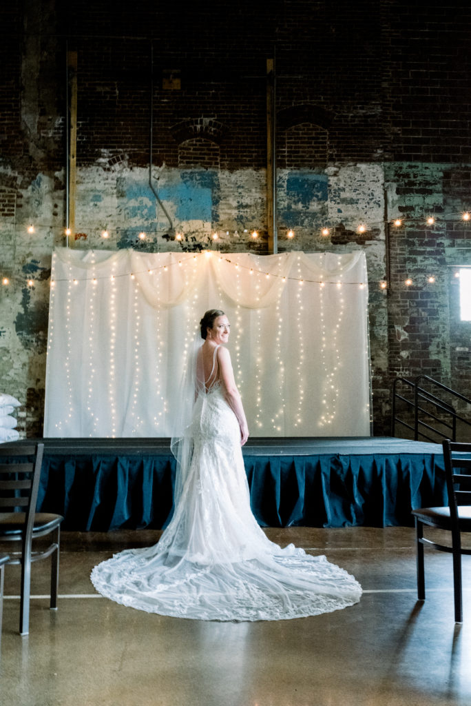 Photo of the bride in her wedding dress in front of the stage where she would be married. Party lights hang from the ceiling, layers of paint from plays past on the exposed brick wall behind her.