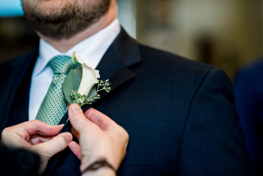 Wedding planner pinning on the groom's boutonniere before the wedding ceremony.