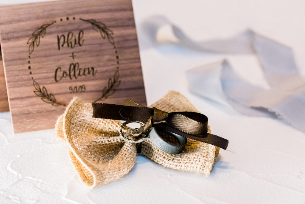Detail photo of the bride and groom's wedding bands tied to a burlap bow and styled in front of the wooden box the couple had made for their wedding day.